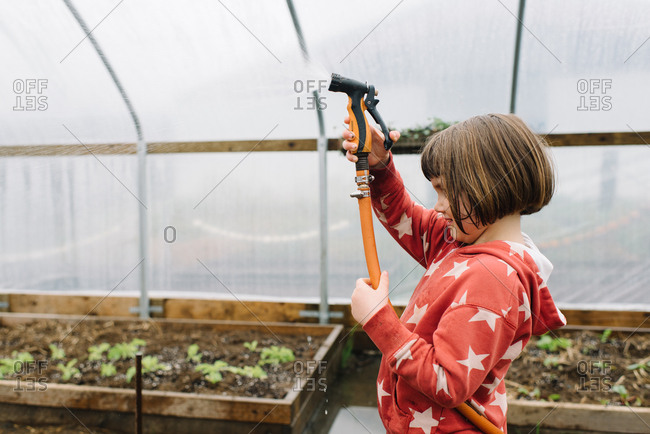 Side profile of little girl spraying water hose in greenhouse