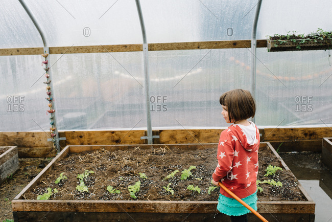 Girl watering plants in greenhouse