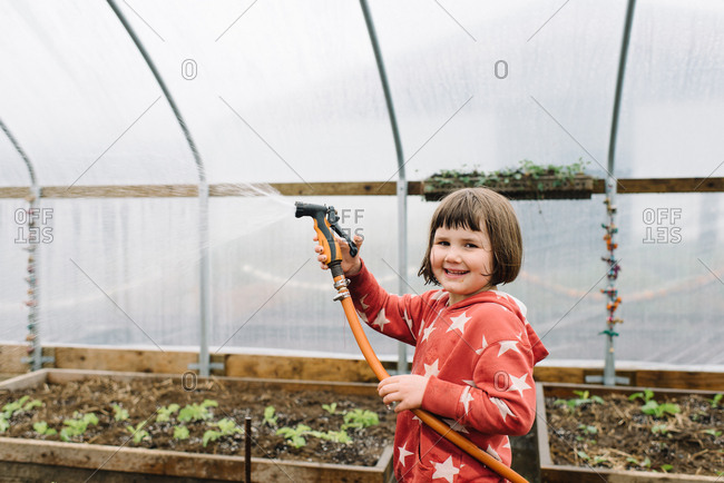 Young girl in greenhouse garden smiling with water house