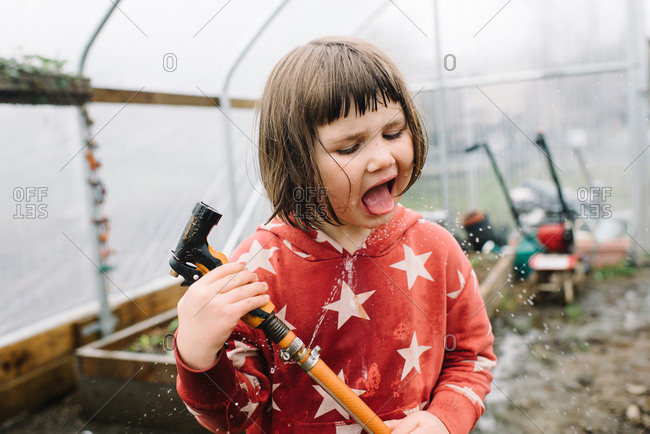 Brunette girl drinking from water hose while gardening in greenhouse