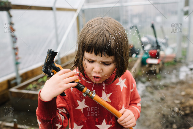Young girl playing with splashing water hose in greenhouse