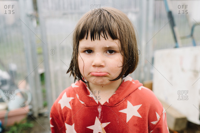 Portrait of little girl pouting in greenhouse