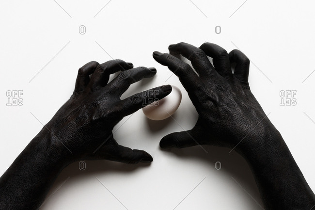 Painted arms and hands reaching towards an egg