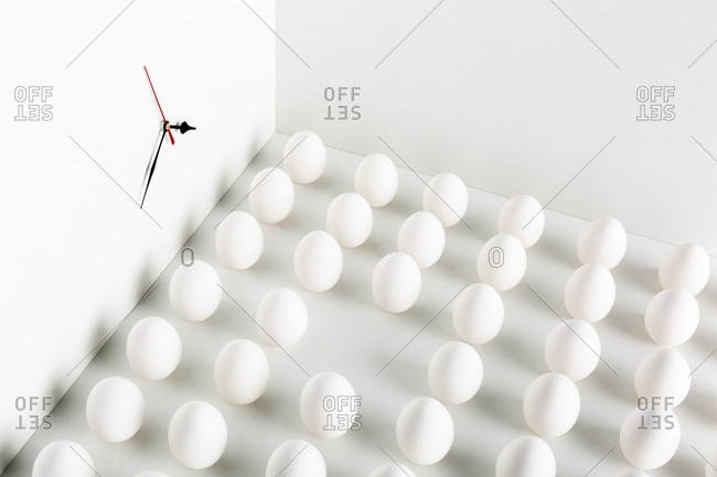 Group of white eggs with clock on the wall
