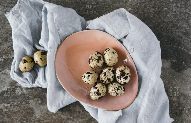 Top down view of quail eggs in a bowl and resting on piece of fabric alongside