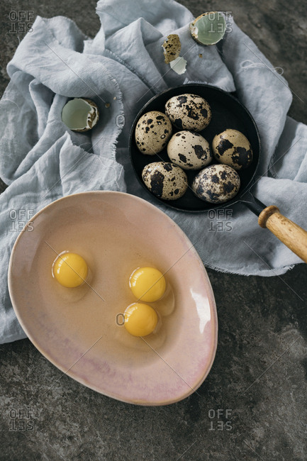Overhead view of whole quail eggs in skillet and cracked into bowl