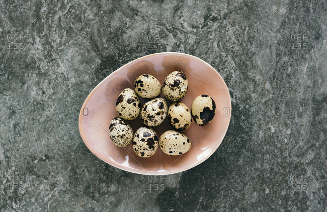 Looking down on oval bowl full of quail eggs