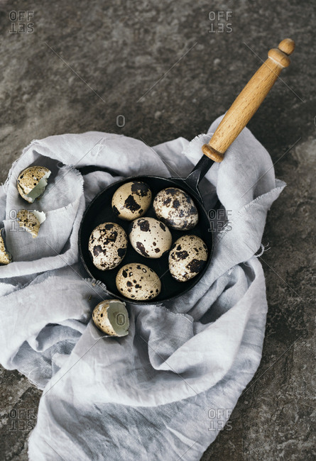 Top down view of whole quail eggs in small skillet and broken shells alongside