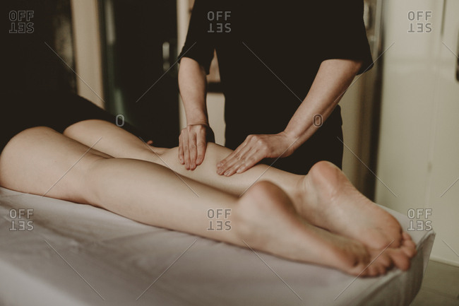 Massage therapist giving client lower leg massage in spa