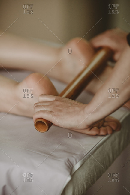 Close up of massage therapist using roller on soles of  feet of female client