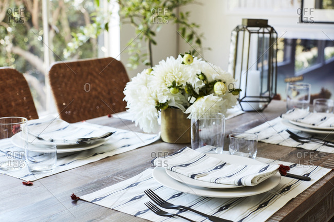 Set table with cloth napkins, placemats, and floral centerpiece