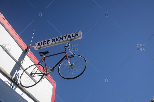 Bicycle hanging on sign outside of rental store