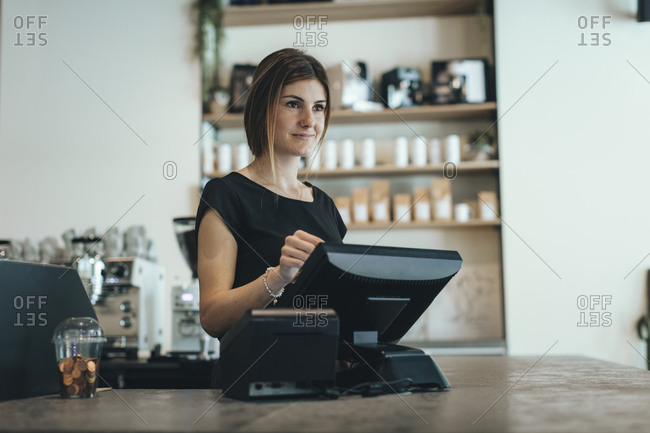Woman working with computer at coffee bar counter
