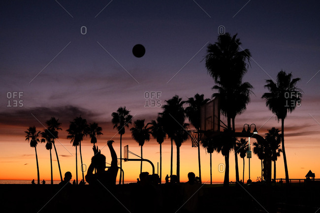 Silhouette of basketball game at sunset at the beach in Los Angeles, California