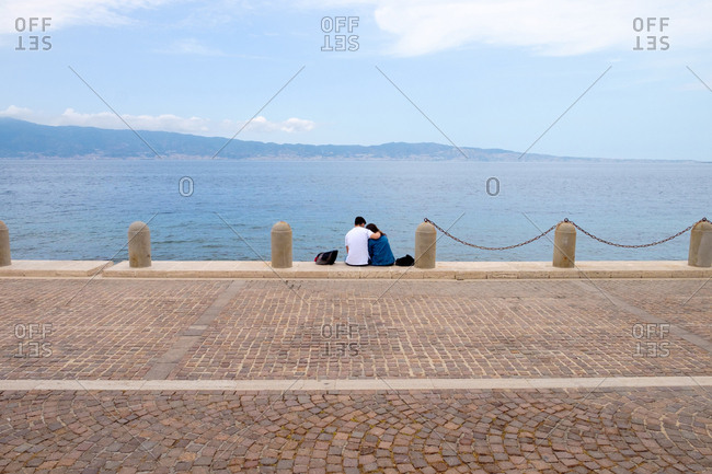 Couple sitting together on promenade overlooking the ocean with their arms around each other