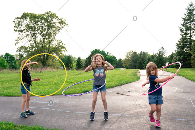 Sisters play with hula hoops at the park