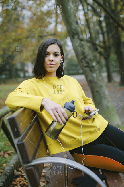Sporty young woman on outdoor autumn fitness workout taking a break for drinking water and listening music from smart phone