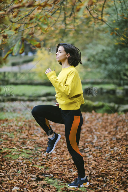 Sporty woman running in place at city park in autumn Female athlete exercising outdoor