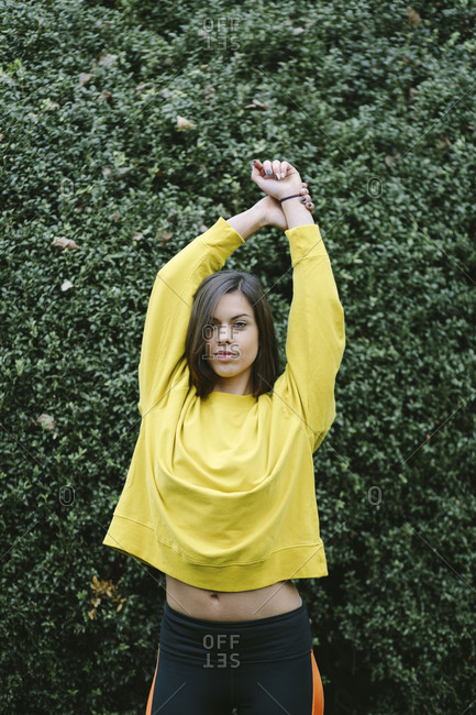 Sporty young woman stretching arms in autumn