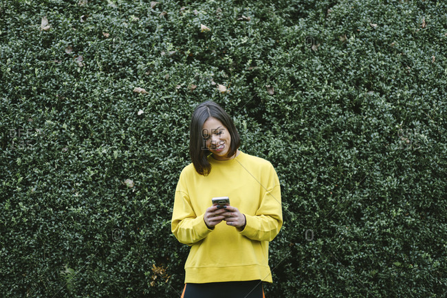 Cheerful sporty woman texting on smart phone in autumn at the park