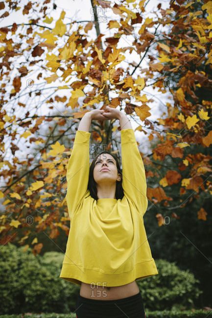 Sporty young woman doing stretching relaxing and breathing exercise under a tree in autumn at city park
