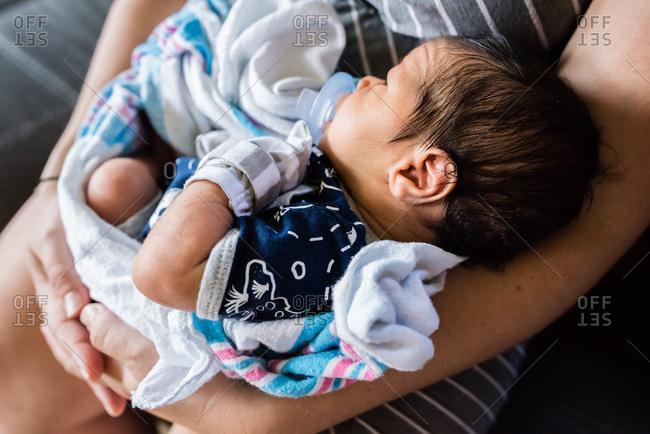 Newborn baby boy held in mother's lap