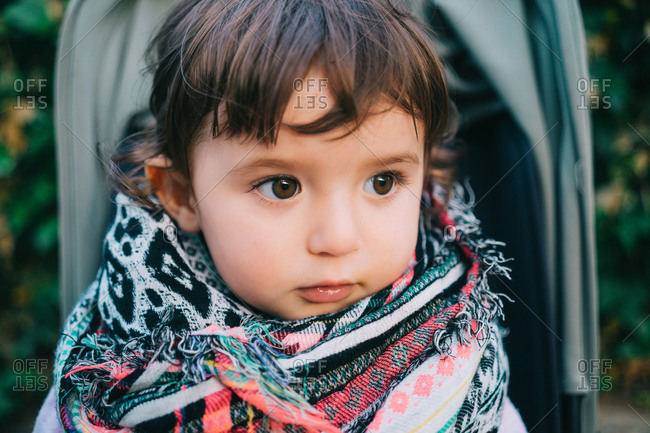Cute one-year-old baby girl with colorful scarf sitting on a stroller