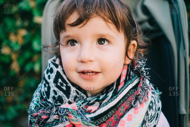Cute one-year-old baby girl with colorful scarf sitting on a stroller and looking up