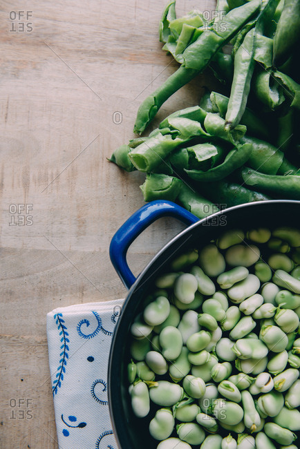 Casserole with broad beans recently peeled on a wooden mango table