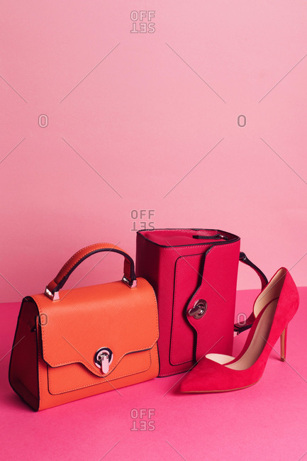 Studio shot of luxury handbags and single high heeled shoe on pink background
