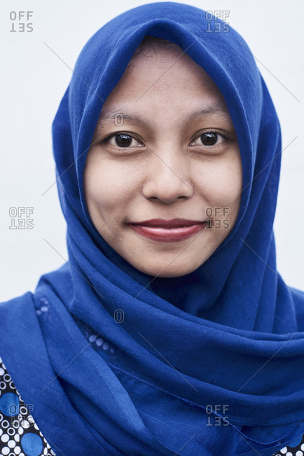 Bandung, Indonesia - April 1, 2018: Portrait of a young adult Muslim female wearing blue hijab, looking serious against white wall