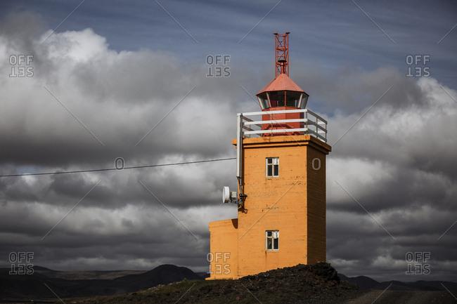 Bright orange lighthouse lit up by sun in the dark skies of Grindavik, Iceland