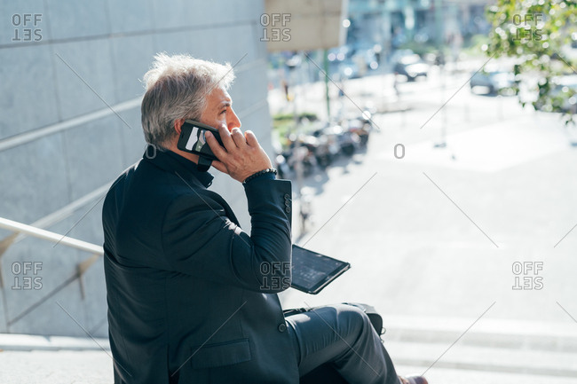 Middle-age contemporary businessman sitting outdoors and talking on a smart phone