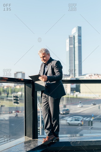 Middle-age contemporary businessman using tablet outdoors in the city