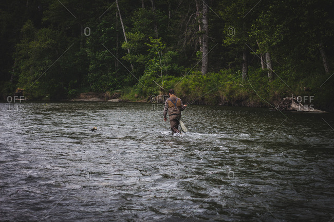 Fisherman wading downriver in remote area