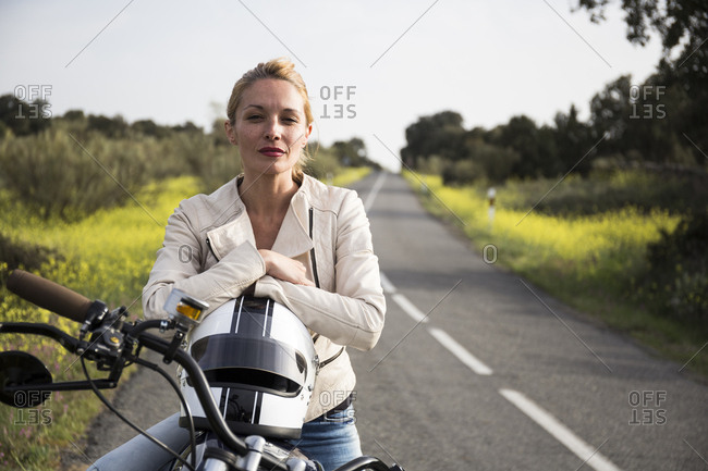 Woman on a motorbike looking at camera on a road in Madrid, Spain