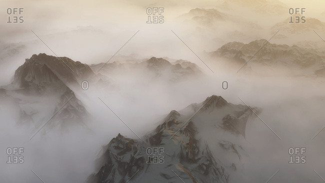 Snowy mountain peaks in clouds at sunrise. High angle view.