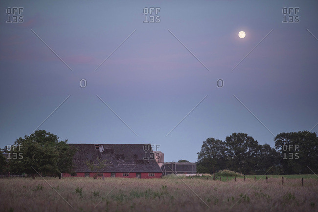 Barn with trees in meadow under sky with moon at twilight.