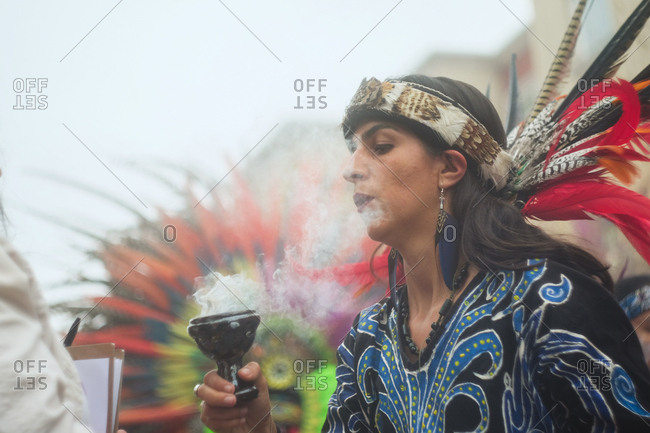 Oakland, California, USA - October 29, 2017: Woman wearing traditional native costume burning incense at Day of the Dead festival