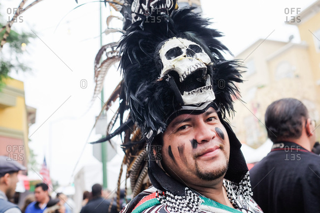 Oakland, California, USA - October 29, 2017: Portrait of a man wearing a traditional headdress costume with skull at Day of the Dead festival