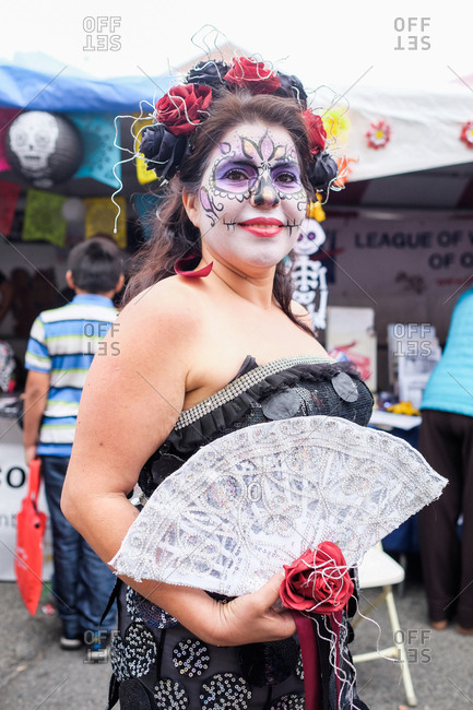 Oakland, California, USA - October 29, 2017: Woman with face painted holding fan at Day of the Dead festival