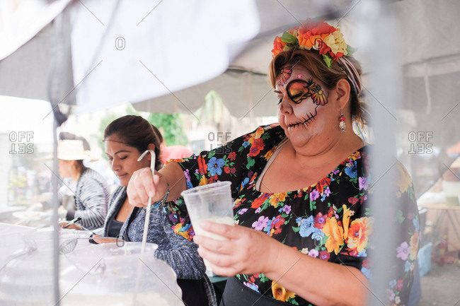 Oakland, California, USA - October 29, 2017: Woman with painted face serving horchata at Day of the Dead festival