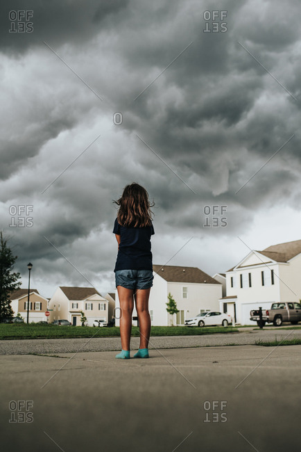 Girl standing on sidewalk watching storm clouds