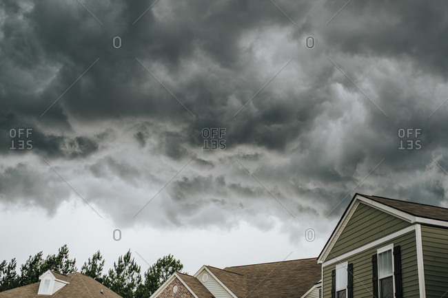 Dark storm clouds above neighborhood rooftops