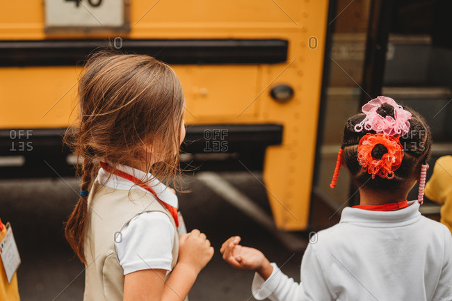Little girls waiting to get on school bus