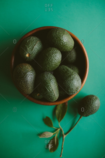 Wooden bowl of avocados on green background