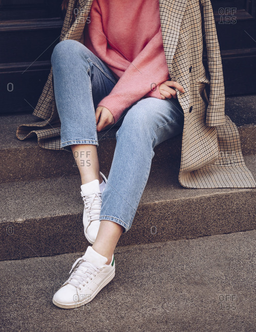 Lower detail of a woman wearing a pink soft sweater and a houndstooth pattern coat with jeans and white sneakers