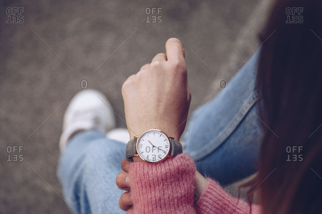 Detail of a fashion blogger wearing a pink sweater and a golden watch