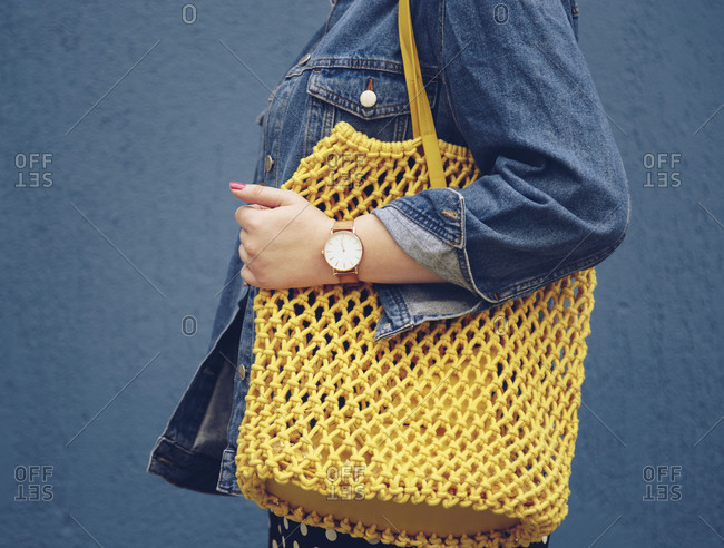 Street style fashion detail, close-up of a woman wearing a denim jacket, yellow tote net bag and an analog wrist watch