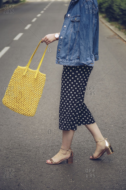 Stylish woman crossing the street and swinging her net tote bag